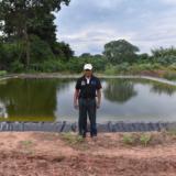 Lucio Flores junto al reservorio de agua en su cultivo